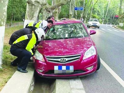 交警和过路市民齐心协力抬起陷入排水沟的车辆。 南报融媒体记者 王茸摄