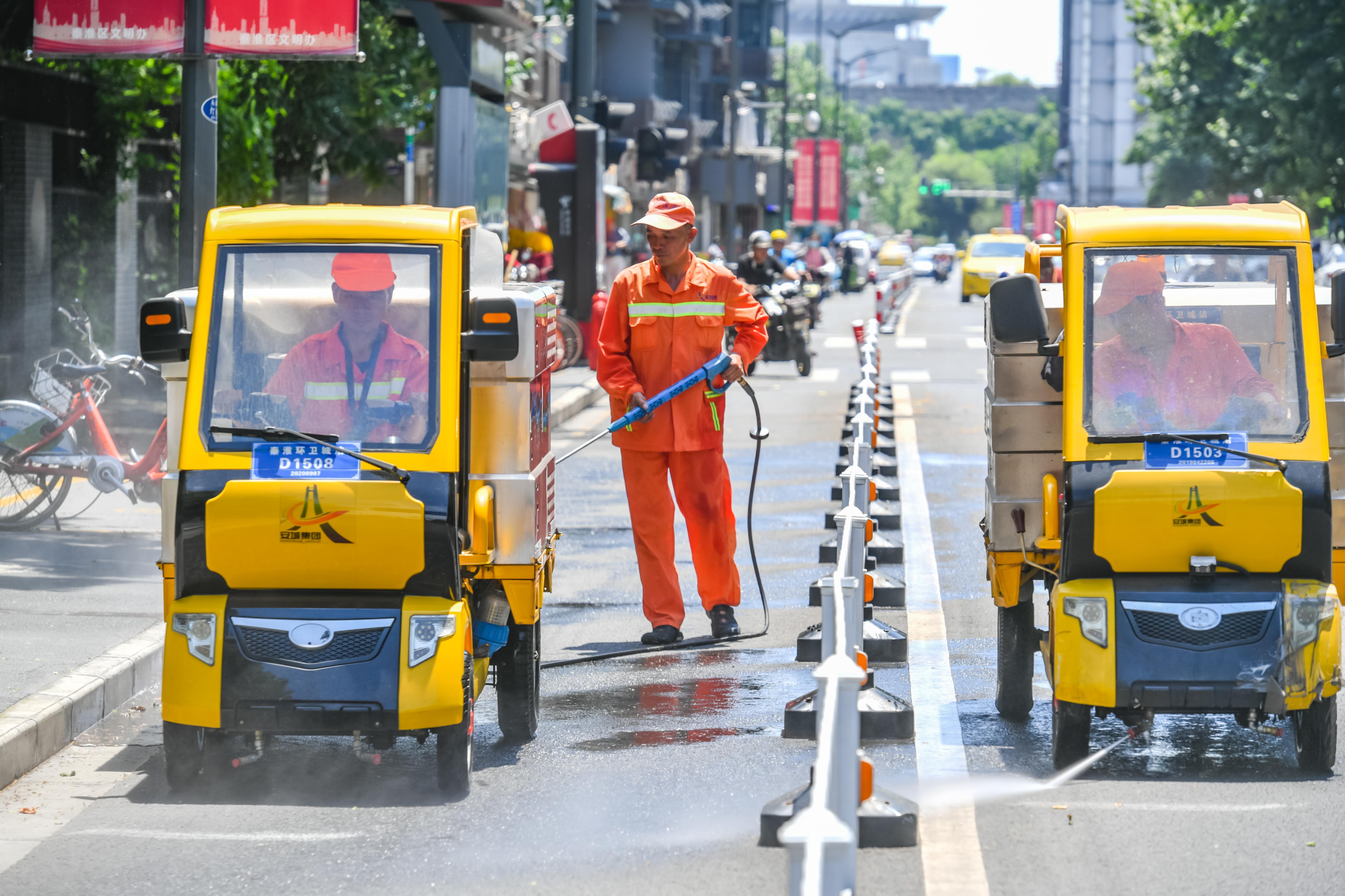 7月12日,我市最高气温达到37℃,有些马路地表温度已达到45℃,气象部门发布高温橙色预警。在马道街,环卫工人冒着酷暑,反复清洗道路和马路中的护栏。 南报融媒体记者 董家训 摄