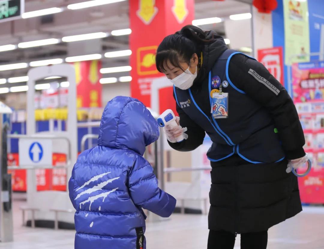 南京众多商场超市多措并举做好防疫工作,图为1月8日栖霞区和燕路沃尔玛购物广场,工作人员为消费者测量体温。南报融媒体记者 徐琦摄