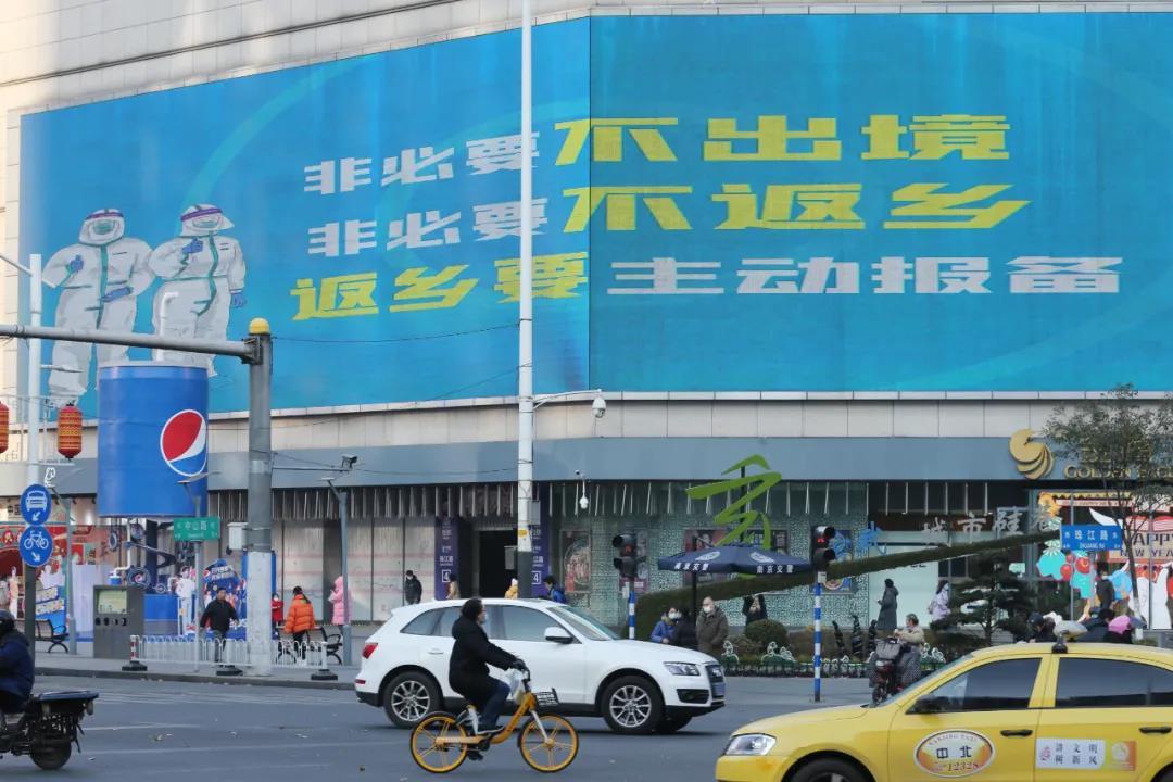 """1月19日,南京珠江路一處大型戶外廣告屏播放倡導""""就地過年""""的公益廣告。南報融媒體記者 徐琦攝"""