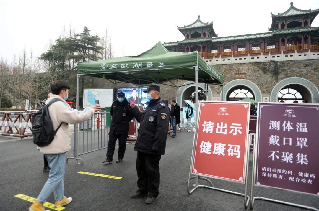 1月25日,在玄武湖公園的入口處,工作人員提示入園游客佩戴好口罩、出示健康碼、保持距離不聚集,并進行現場紅外測體溫。南報融媒體記者 杜文雙攝